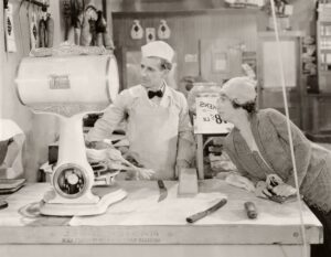 Black and white retro photo of woman flirting with her butcher and trying to get him to buy equity indexed annuities