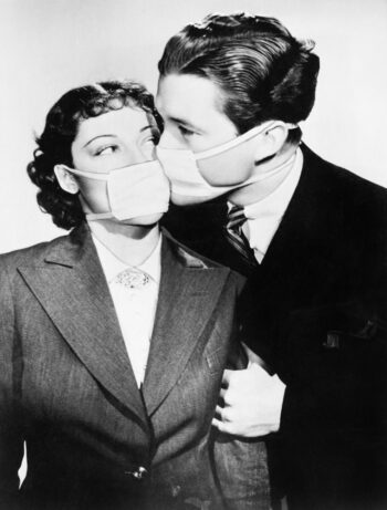 Retro black and white photo of a man and woman in business attire kissing through their masks.