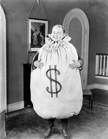 Retro black and white photo of man encased in a drawstring bag with a big dollar sign on it, i.e., Mr. Money Bags.