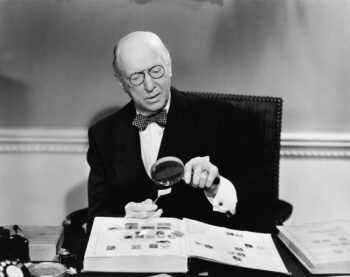 Vintage black and white photo of man looking at the fine print of an equity indexed annuity with a magnifying glass..