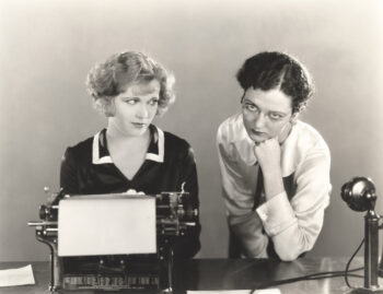Black and white vintage photo of two secretaries sitting at the typewriter looking disgusted as they try to understand equity indexed annuities.