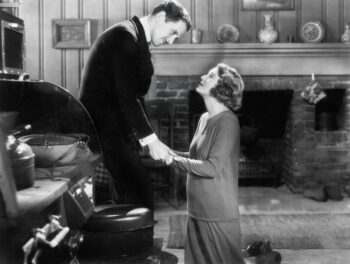Retro black and white photo of man standing and woman kneeling him begging him to get her out of her equity indexed annuity.
