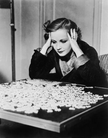 Black and white retro photo of young woman holding her head in confusion as she stares at pieces of a jig saw puzzle, which is analogous to all the combinations of contract exclusions with an equity index annuity.