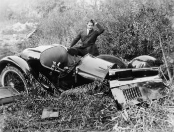Black and white retro photo of a man staring at his crashed car.