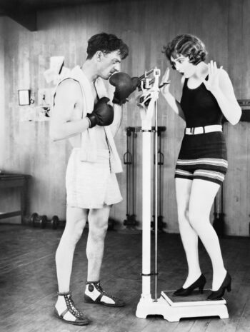 black and white photo of young woman shocked at her weight with a man in boxing gloves