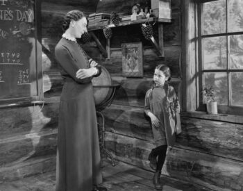 Vintage black and white photo of stern mother talking to child, demanding a decision.