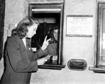 Retro black and white photo of a woman at a box office window ordering two fixed annuities: first a MYGA then one with a guaranteed rate.