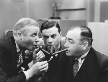 Retro black and white photo of three men using one match to light three cigars as they celebrate the taxes they deferred with their fixed annuity.