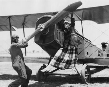 Retro black and white photo of a woman in a skirt and pilot in a jump suit tring to get the propellers of a bi-plane started.