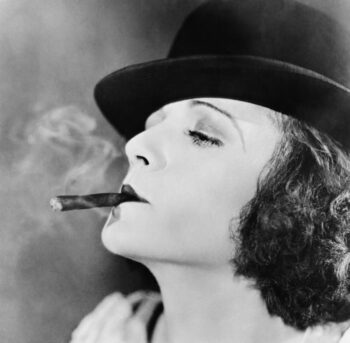Retro black and white photo of woman smoking a cigar, with her nose in the air, saying she's seen it all--including GameStop.