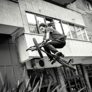 Black and white photo of a boy doing stunts on his BMX bike symbolizing he's riding GameStop to the moon.