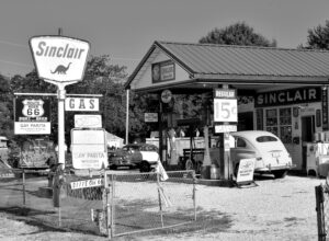 Retro black and white photo of a gas station and car at the pump.