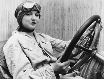 Retro photo of a female driver sitting at the wheel looking worried her GameStop short sale is about to go bad.