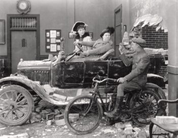 1920s black and white photo of car that's pretended to crash through a wall and a young man on a bike offering them gasoline.