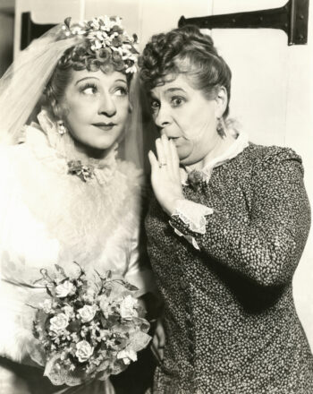 Retro black and white photo of woman whispering to bride wanting to know if she can loan her shares of GameStop.