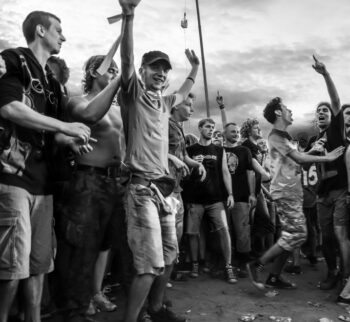 Photo of jubiliant young men with hands in the air, smiling, and having a great time as they contemplate the rising stock price of GameStop.