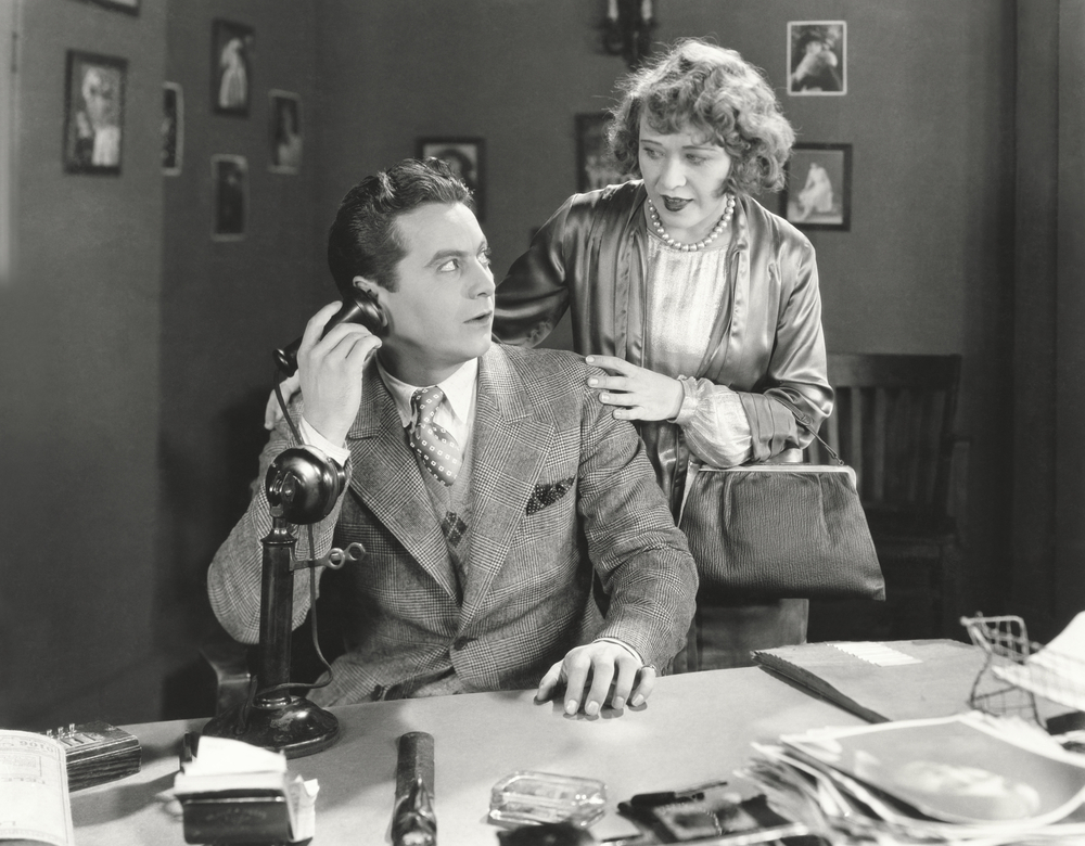 Retro black and white photo of a couple living the millionaire lifestyle by wanting to know if the person on the phone takes competitor coupons.